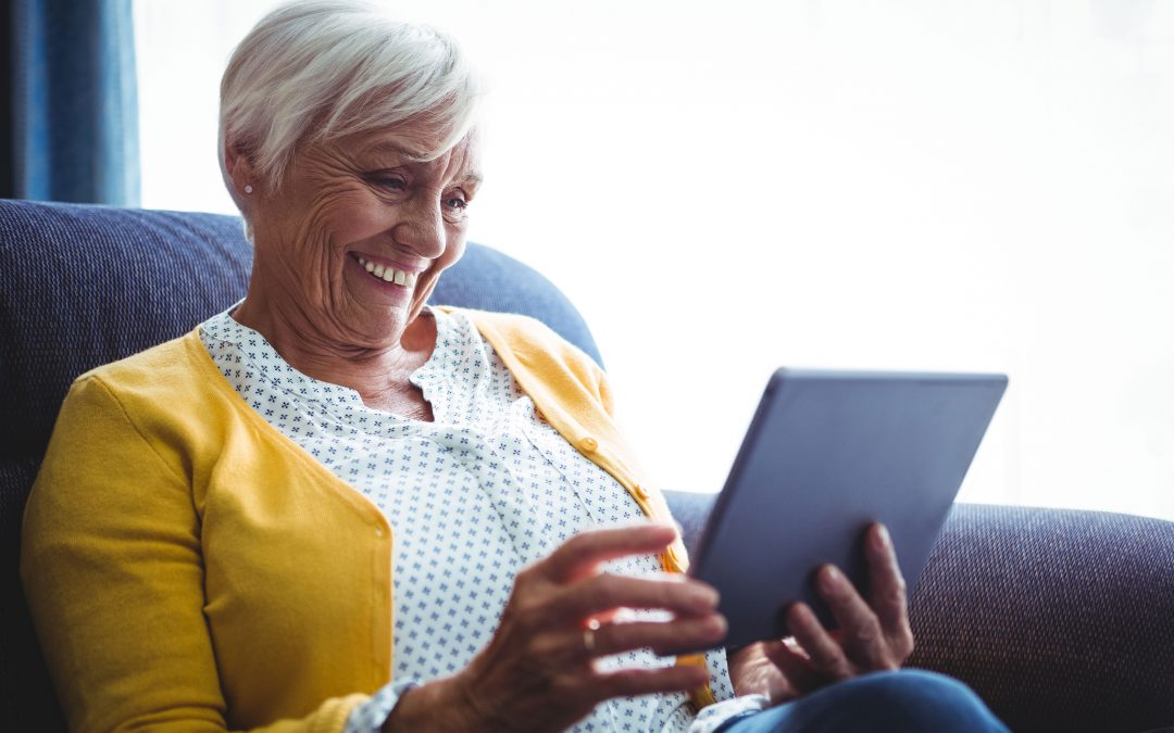 Patient sitter at home reading on a tablet.